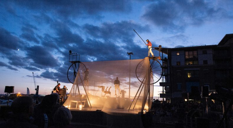 Man holding a long pole whilst balancing on a tightrope high in the air. It is dusk.