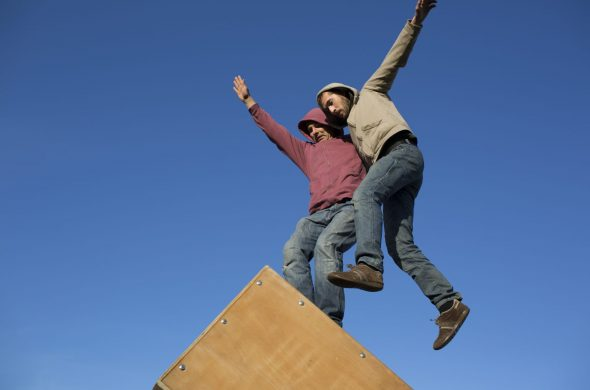 Two men wearing jeans and hoodies balance on a box. The background is blue.