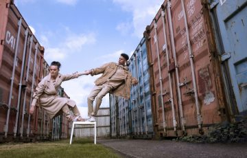 Two dancers hold hands while balancing on a chair. They are surrounded by industrial storage units.