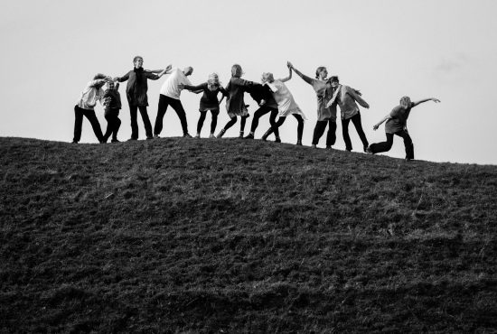 Adults dancing on top of a hill