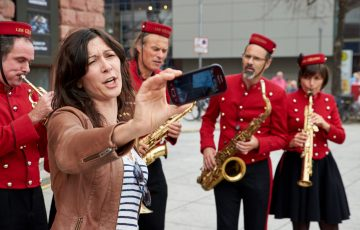 A woman holding her phone to take a photo with a brass band behind her